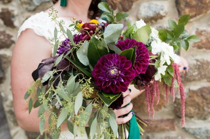 Bridal Bouquet of Blueberry Branches, Magnolia Foliage, Zinnias, Dahlias, Ranunculus, Hanging Amaranthus, Seeded Eucalyptus, Silver Dollar Eucalyptus, Smoke Bush, Scabiosa, Craspedia and Thistle. Image by Posh Moments Photography. Florals by Rachel of Fleur-Di-Re.